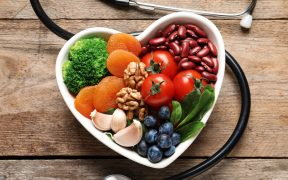 Bowl with products for heart-healthy diet and stethoscope on wooden background, top view